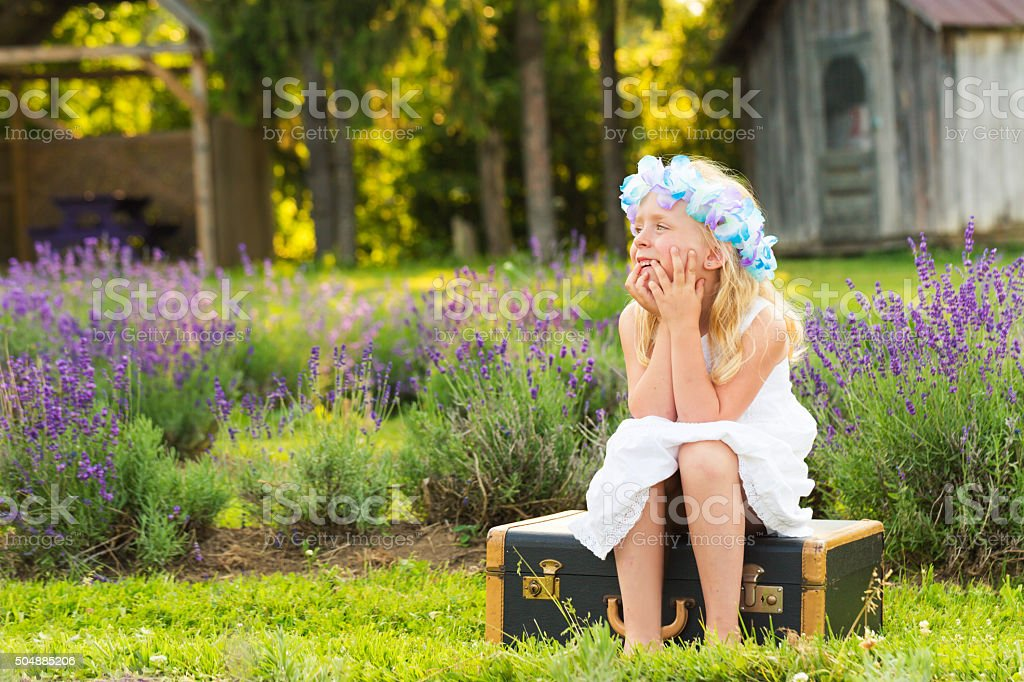 Little girl meditating in a lavender field stock photo