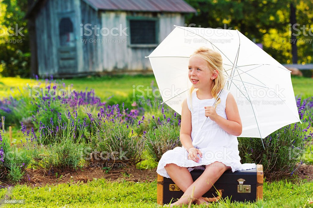 Little girl meditating in a lavender field with umbrella stock photo