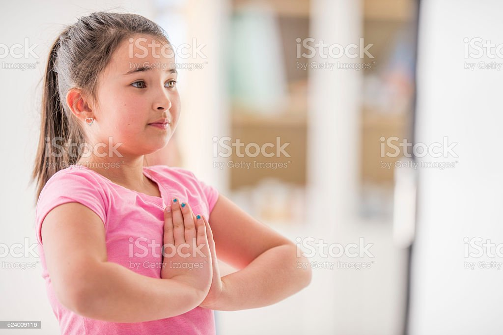 Little Girl Meditating in Class stock photo