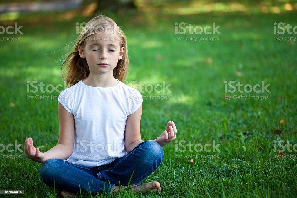 Little girl meditating stock photo