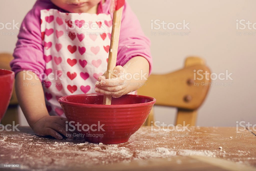 Little Girl Mixing Ingredients in Red Bowl stock photo