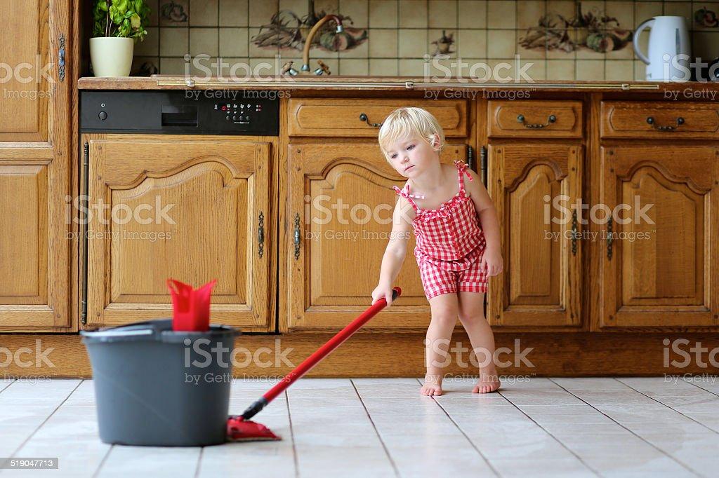 Little girl mopping floor in kitchen stock photo