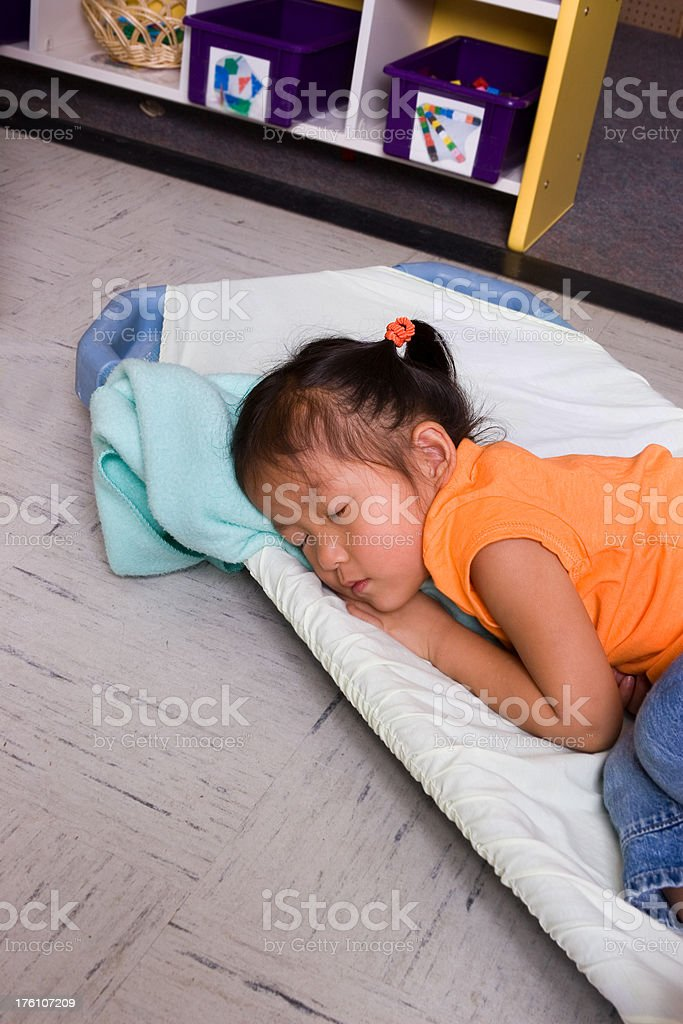 Little girl naps on cot at preschool stock photo