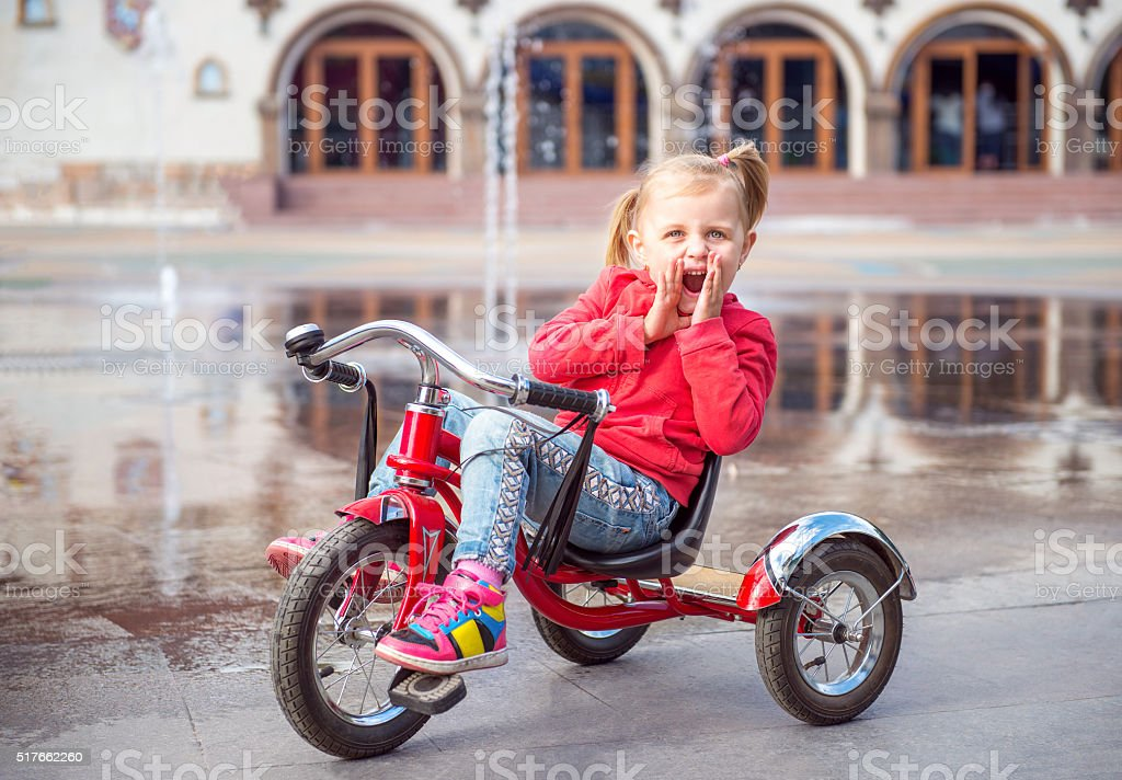 Little girl near fountain riding on tricycle stock photo