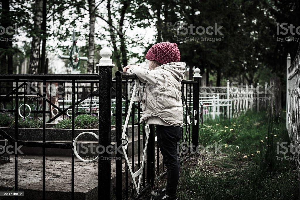 little girl near the grave stock photo