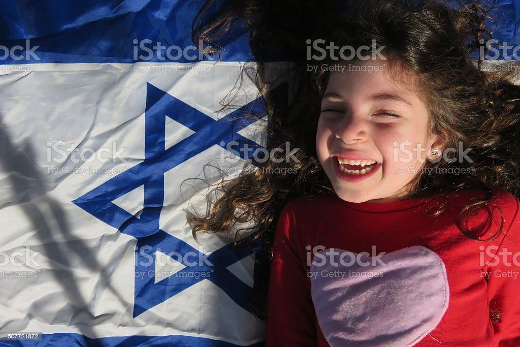 Little girl near the Israeli flag stock photo