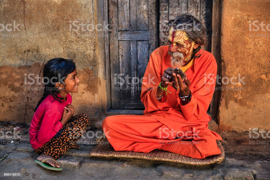 Little girl observing how Sadhu doing doing his makeup stock photo
