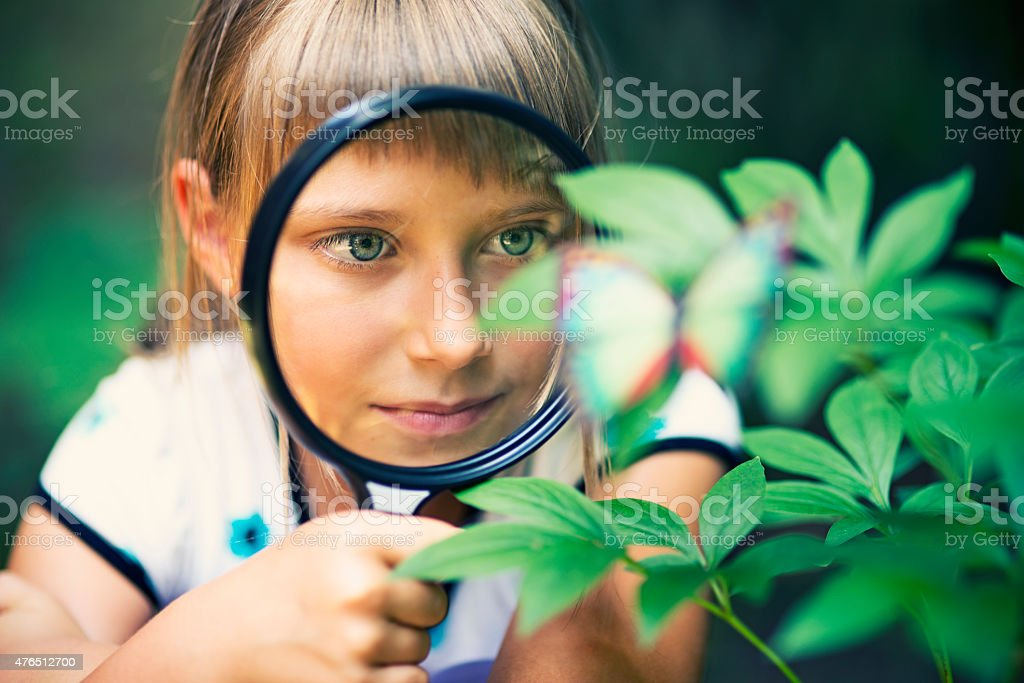 Little girl observing the mysteries of nature. stock photo