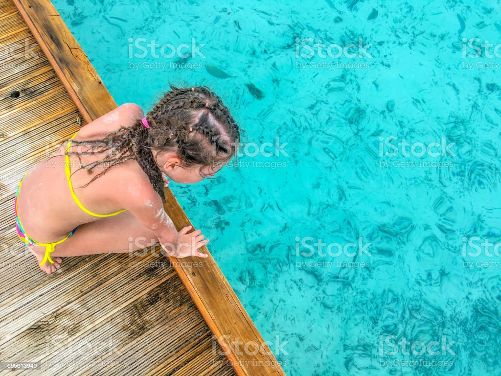 Little Girl Observing The Sea From The Pier stock photo