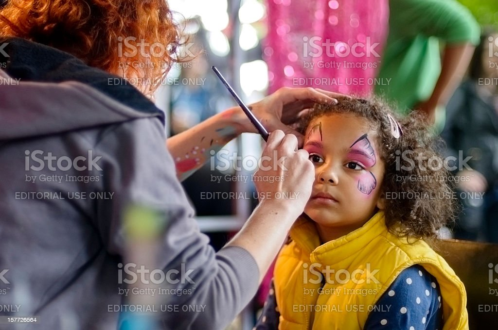 Little Girl of 5 is Getting Her Face Paint, Outdoors royalty-free stock photo