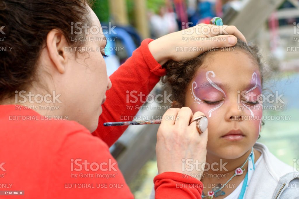 Little Girl of (6-7) is Getting Her Face Paint, Outdoors stock photo