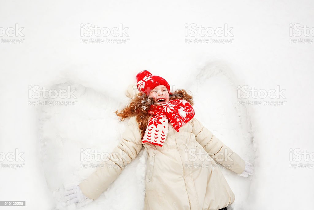 Little girl on a snow showing angel figures. stock photo