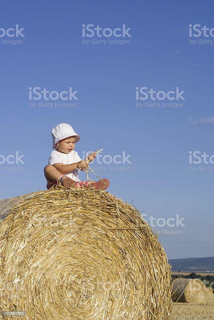 little girl on a straw bale 1 royalty-free stock photo