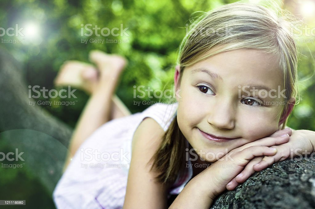 Little girl on a tree branch stock photo