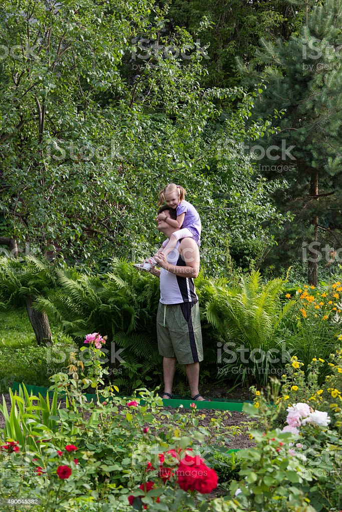 little girl on Daddy shoulders close his eyes stock photo
