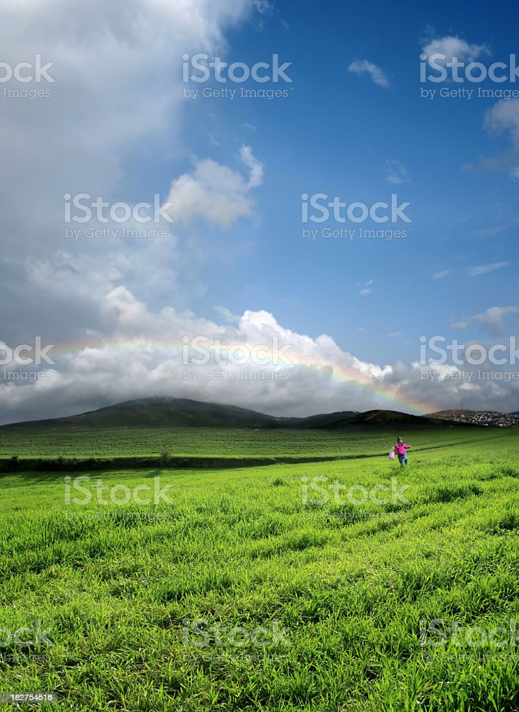 little girl on green landscape and rainbow sky royalty-free stock photo