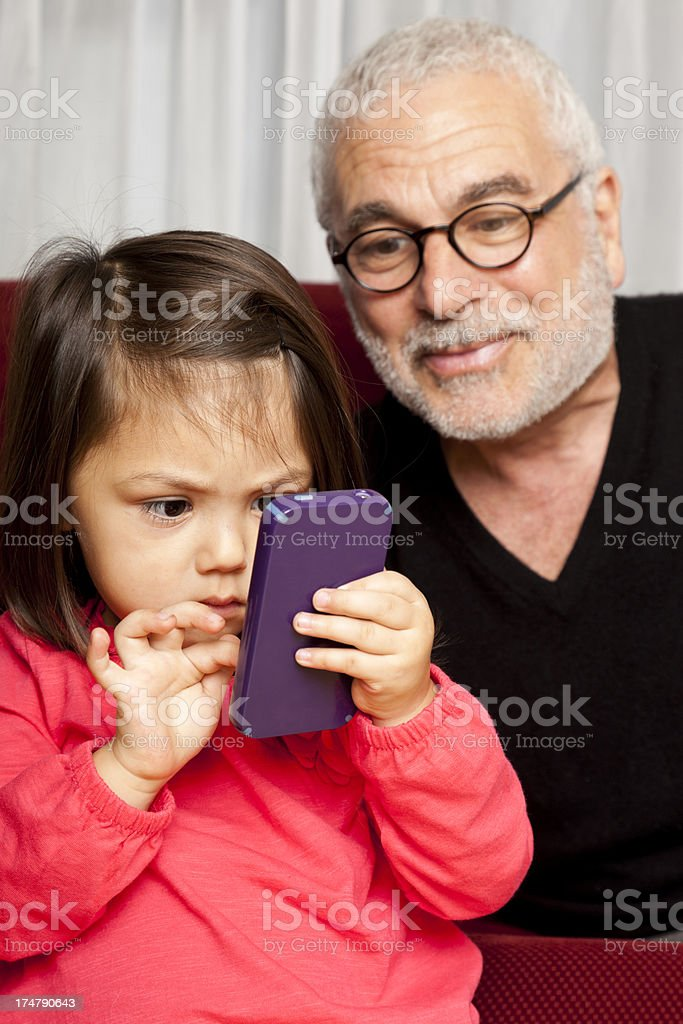 little girl on mobile phone, with grandpa looking over shoulder royalty-free stock photo