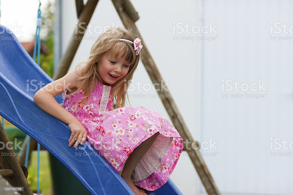 Little girl on slide in summer stock photo