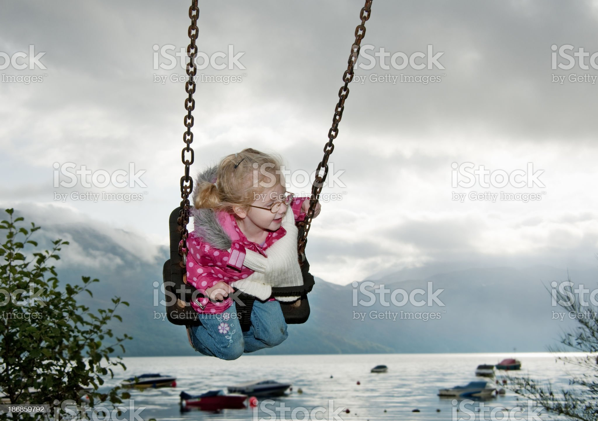 little girl on swing at waterfront royalty-free stock photo