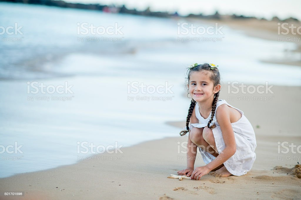 Little Girl on the Beach with a Starfish stock photo