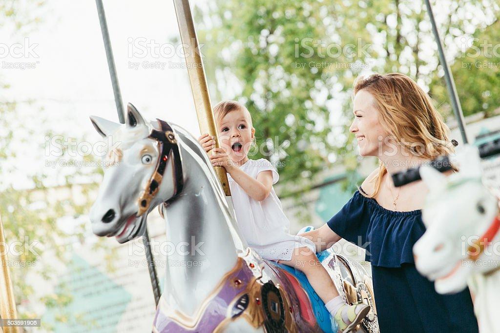 little girl on the carousel stock photo