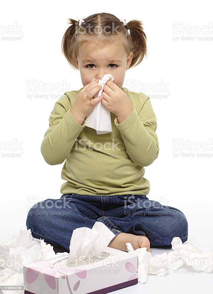 A little girl on the floor blows her nose with a tissue stock photo