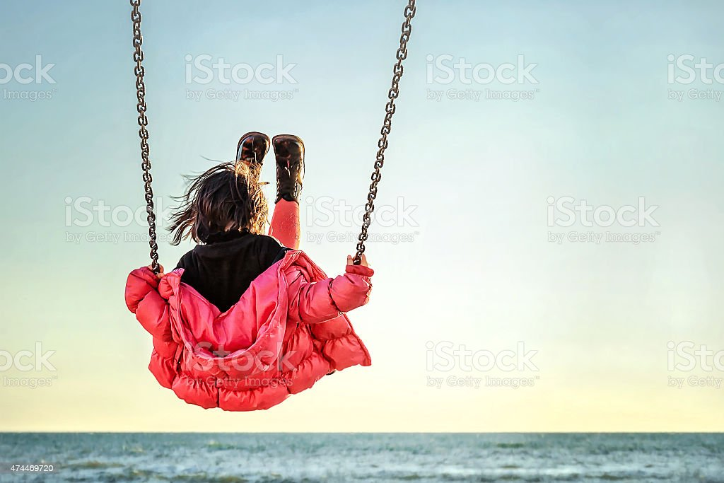 Little girl on the swing stock photo