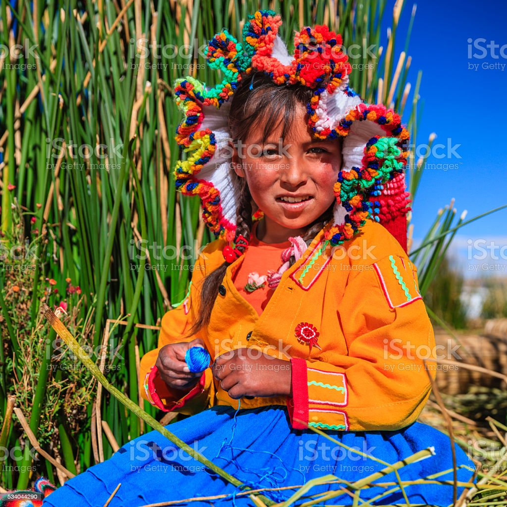 Little girl on Uros floating island selling souvenirs, Lake Tititcaca stock photo