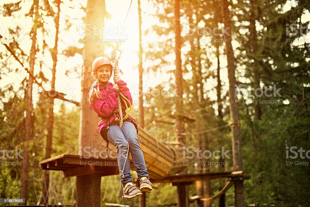 Little girl on zip line in adventure park stock photo