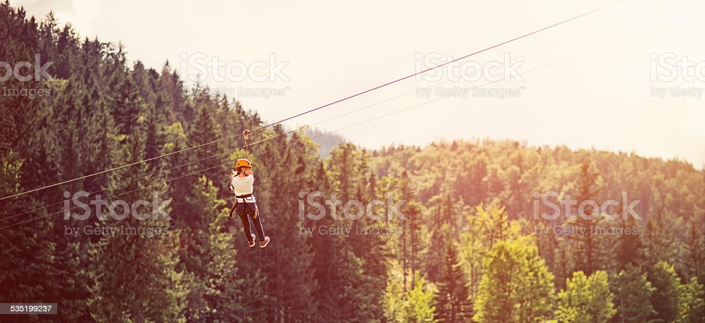 Little girl on zip line in adventure park stock photo
