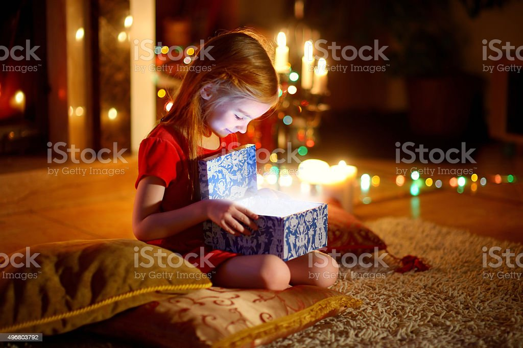 Little girl opening a magical Christmas gift stock photo