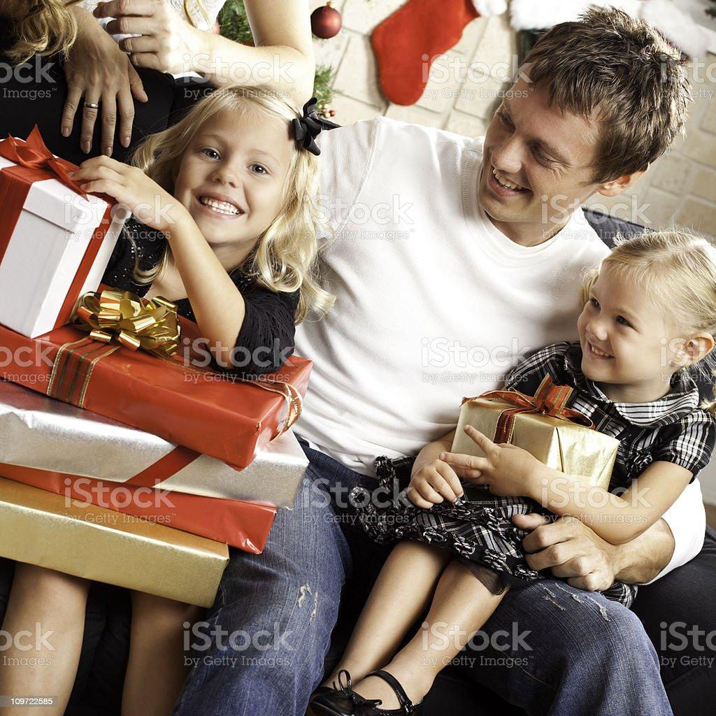 Little Girl Opening Presents on Christmas Day With Family royalty-free stock photo