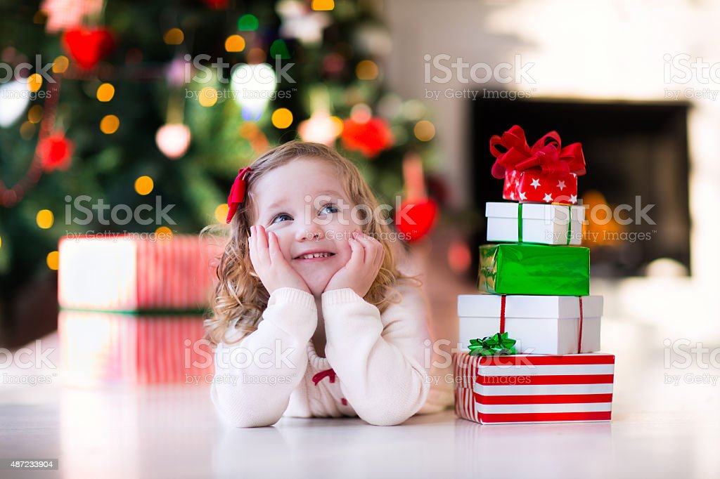 Little girl opening presents on Christmas morning stock photo