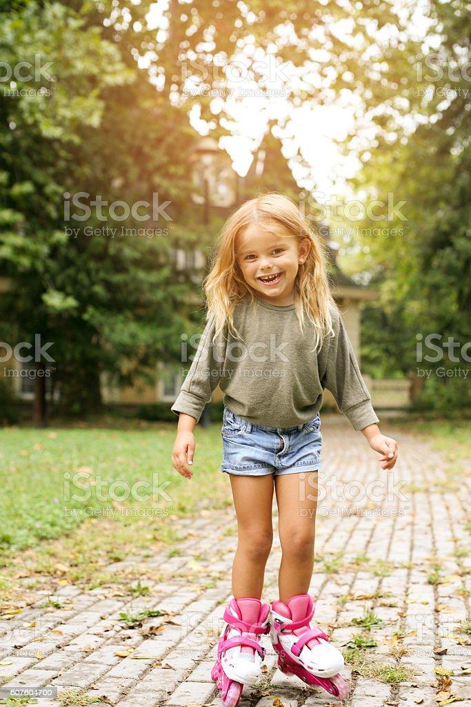 Little girl outdoor rollerblading. stock photo