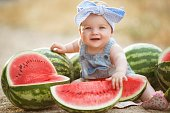 Little girl outdoors with red watermelon