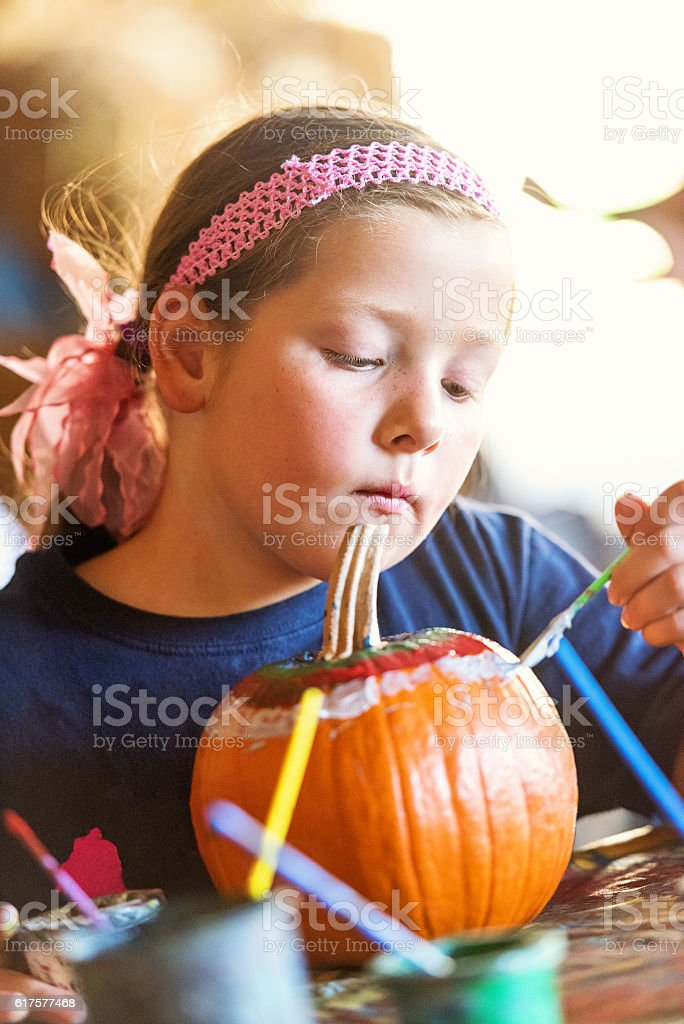 Little girl painting a pumpkin stock photo
