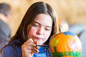 Little girl painting a pumpkin