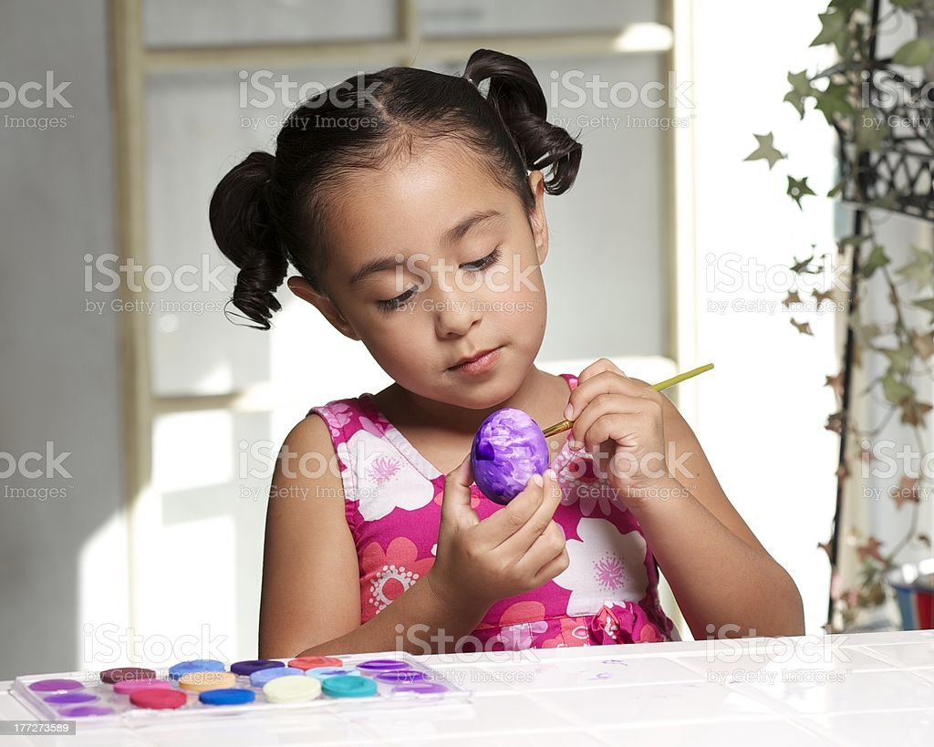 Little girl painting an Easter egg royalty-free stock photo