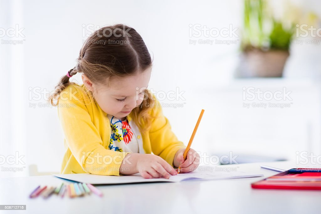Little girl painting and writing stock photo