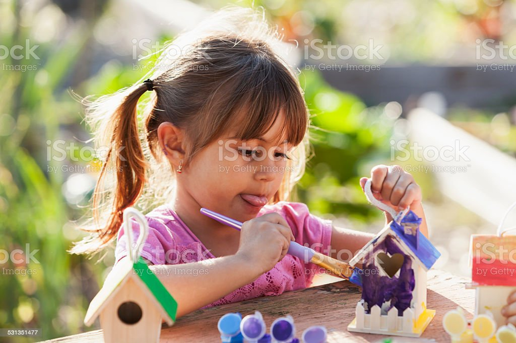Little girl painting bird house stock photo
