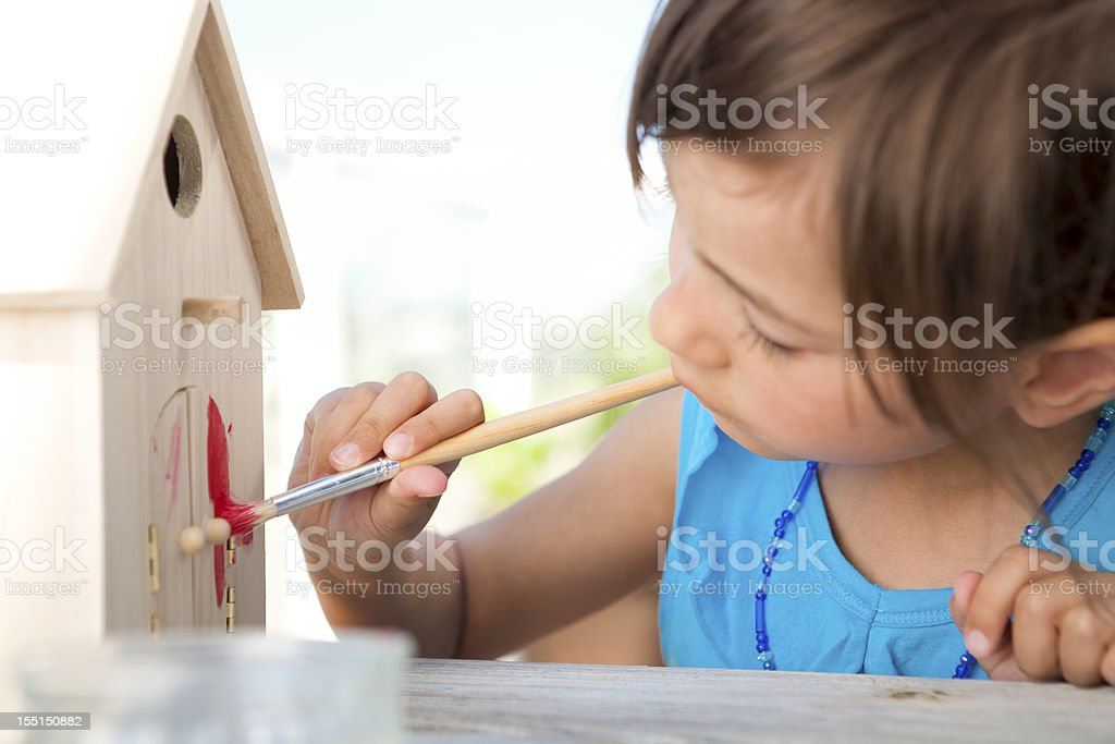Little girl painting birdhouse royalty-free stock photo