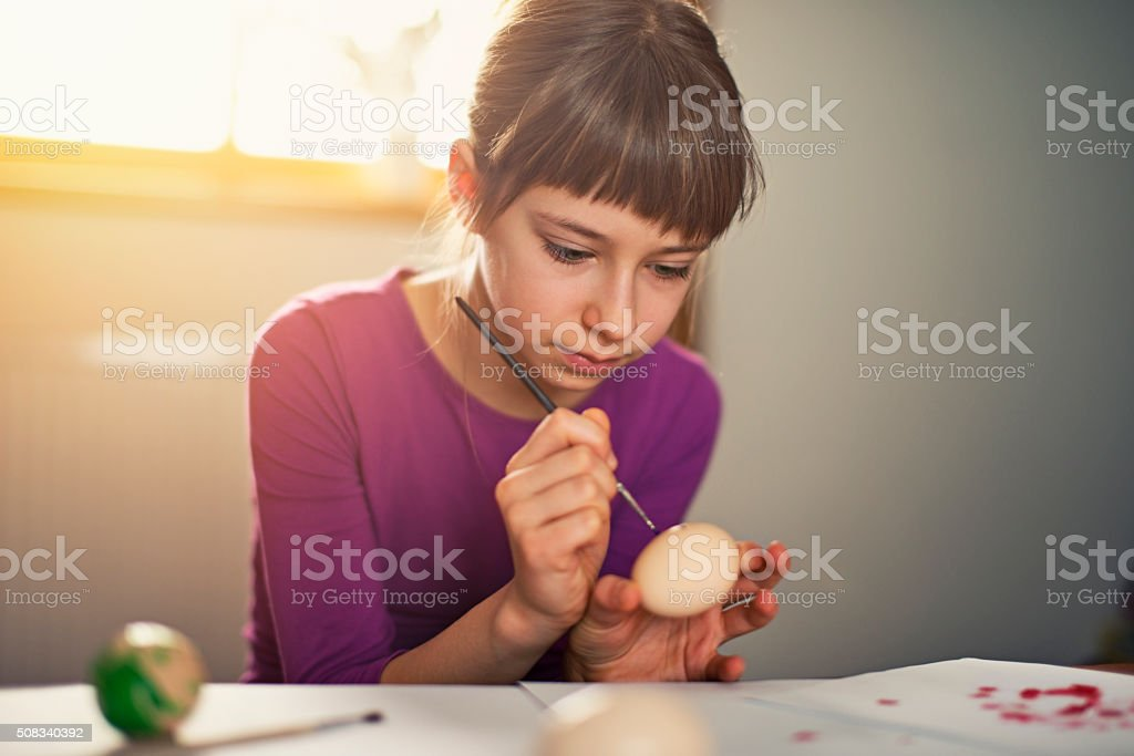 Little girl painting easter eggs stock photo