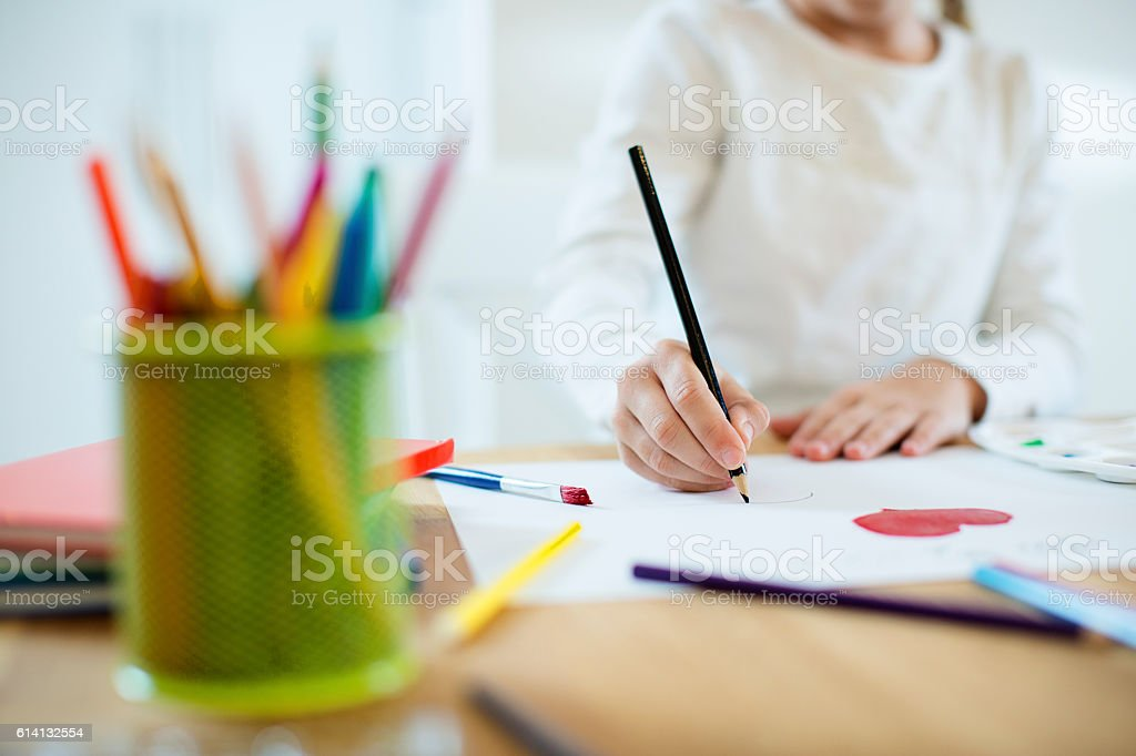 Little girl painting hearts stock photo