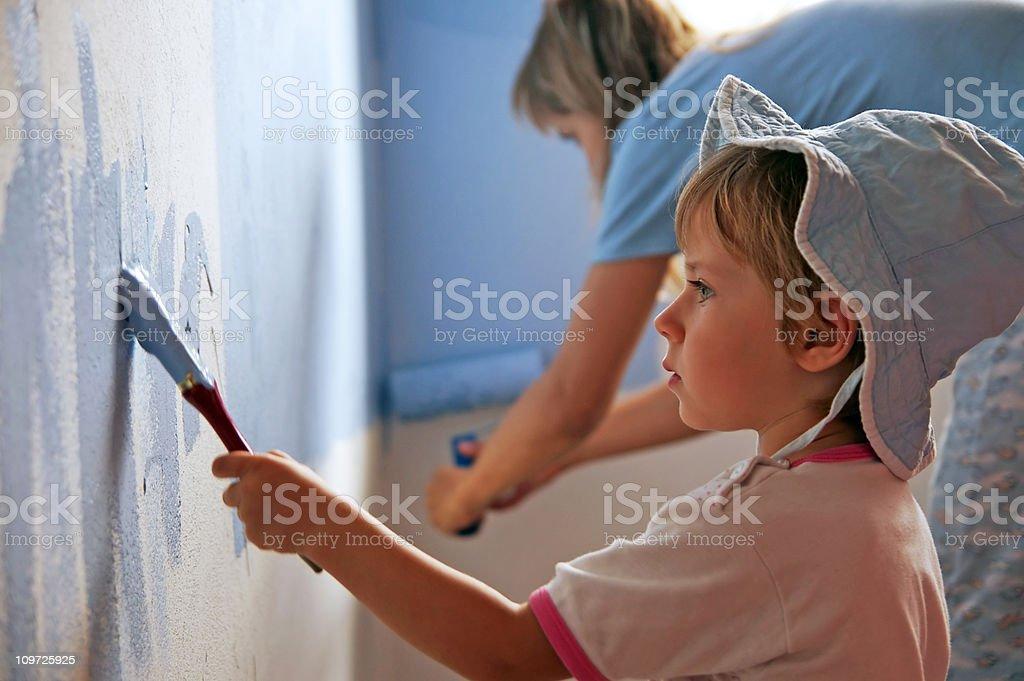 Little girl painting her room stock photo