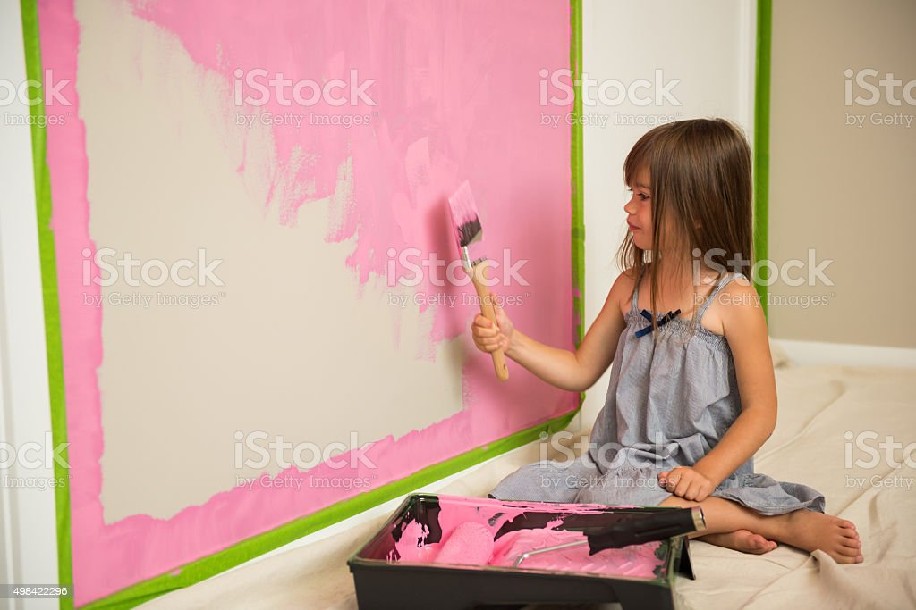 Little girl painting her room pink stock photo