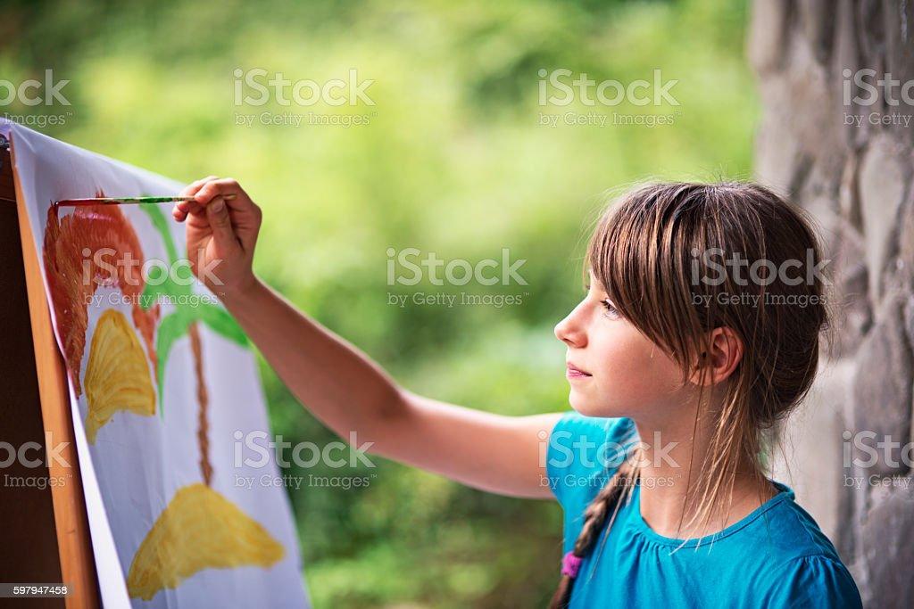 Little girl painting on easel in the garden stock photo