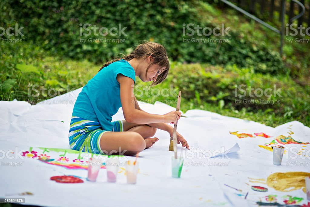 Little girl painting on paper in the garden stock photo