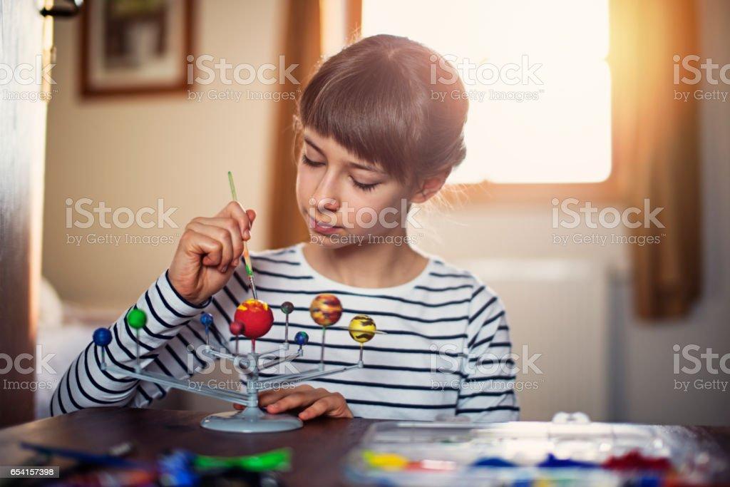 Little girl painting solar system model stock photo