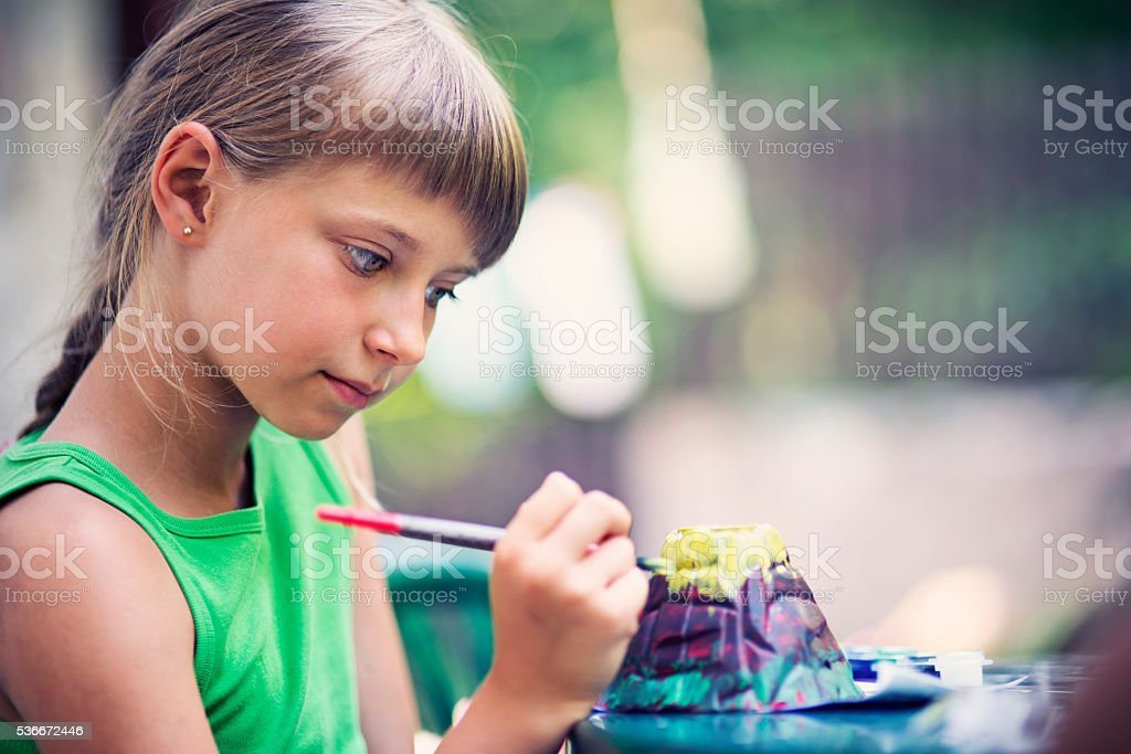Little girl painting volcano school project stock photo