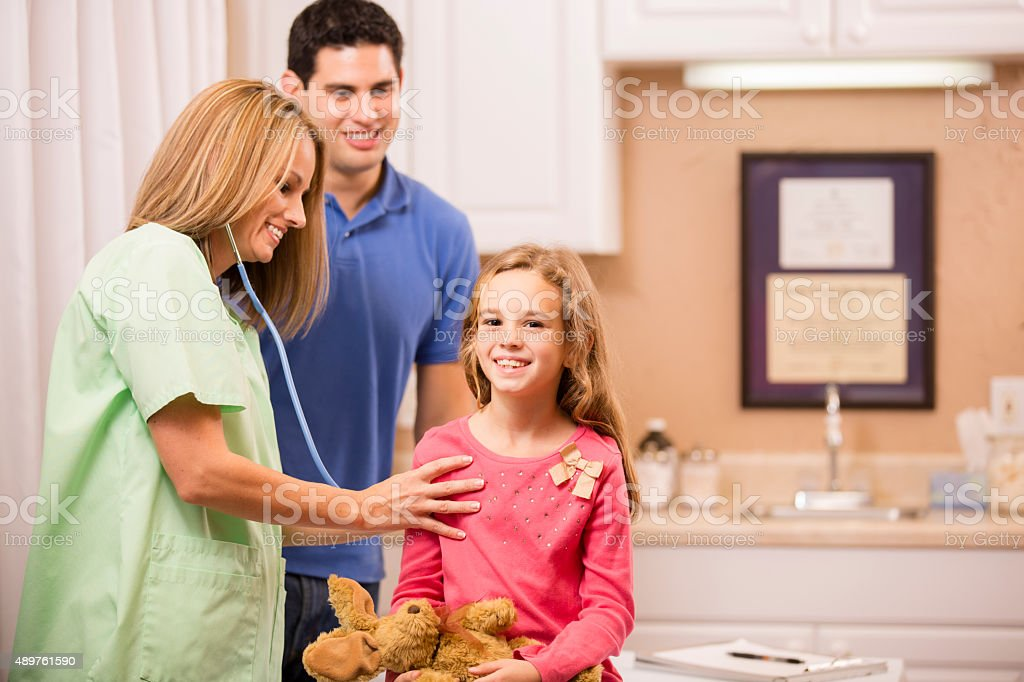 Little girl patient with pediatrician, father. Latin descent. Doctor's office. stock photo
